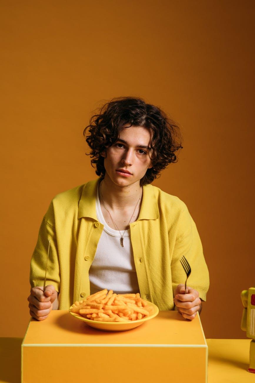 Парень ест картофель фри