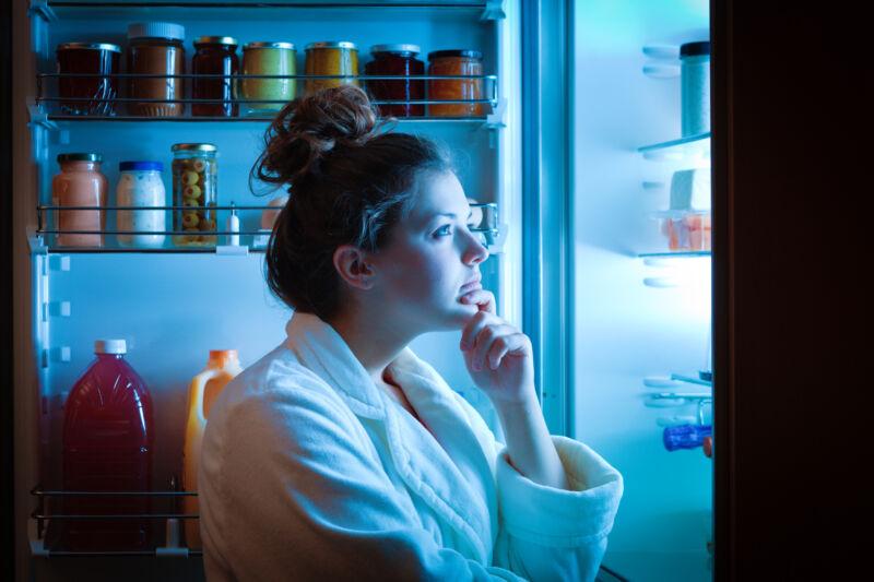 Женщина смотрит в холодильник ночью