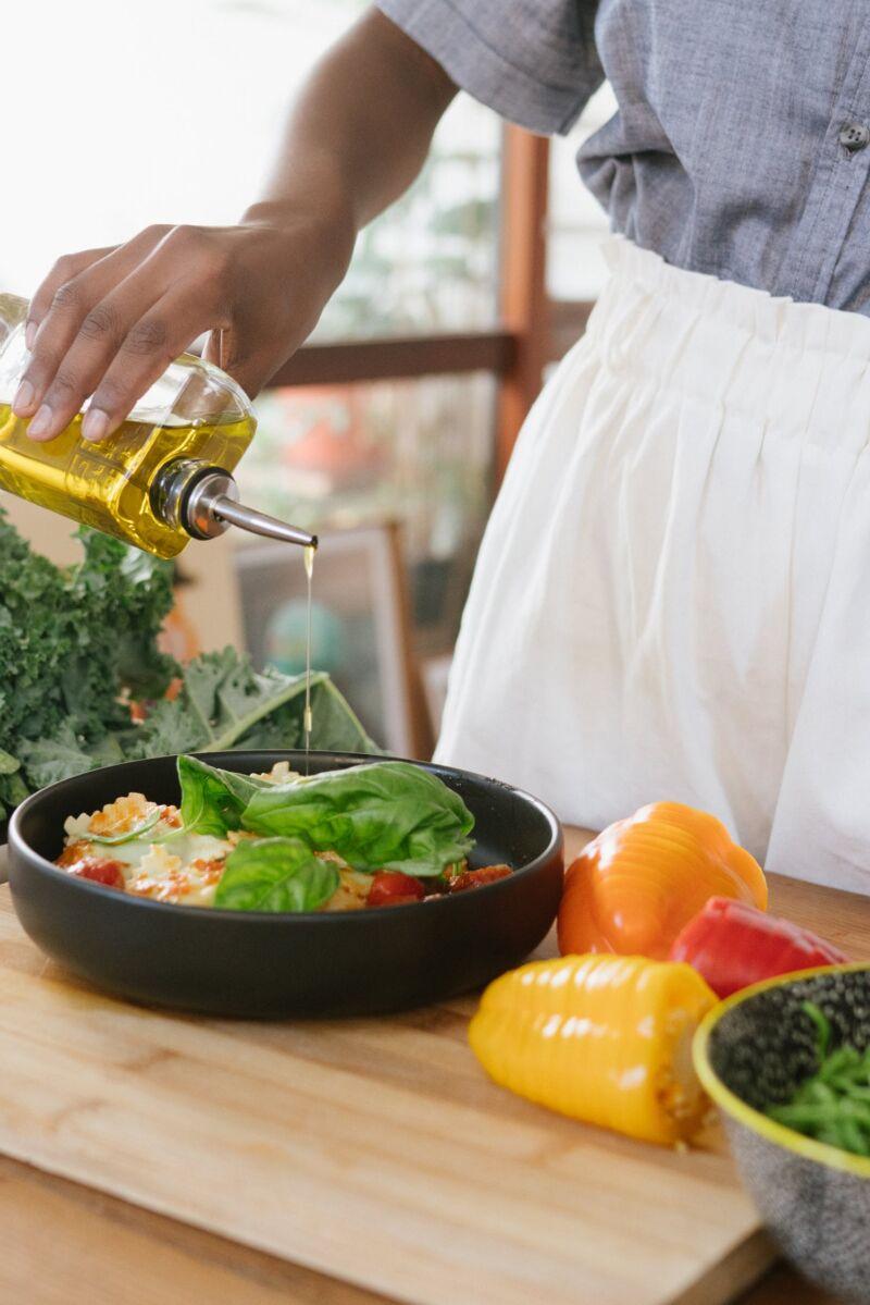 Женщина поливает еду маслом