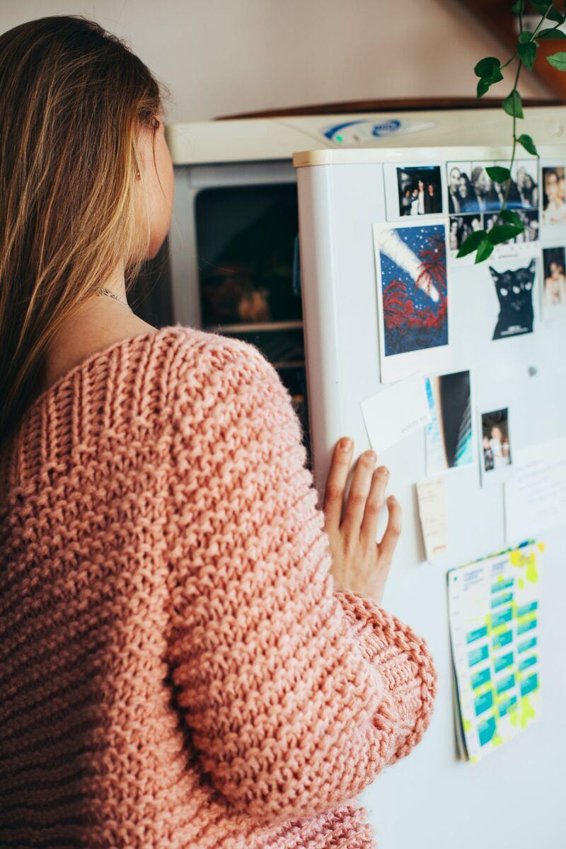 Женщина заглядывает в холодильник