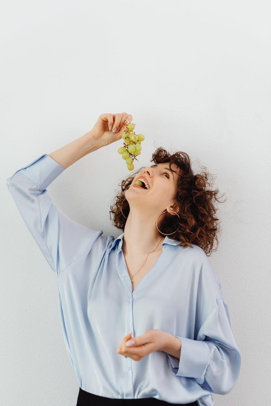 Женщина ест виноград